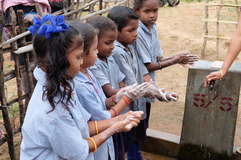 Image of school children washing their hand with water provided by FRANK water
