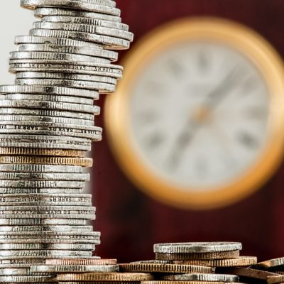 a stack of coins in the foreground with a clock in the background suggesting that a Halcyan water conditioner can save both time and money